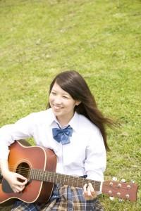 芝に座りギターを弾く女子高生